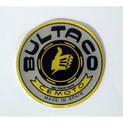 Anagrama deposito Bultaco color gris, borde amarillo.